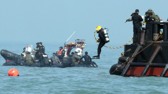 A diver jumps into the sea as recovery operations continue on April 24.