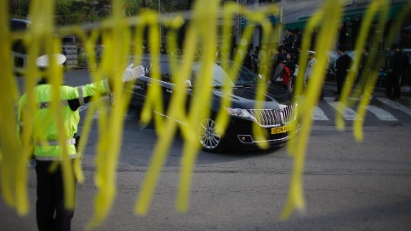 Yellow ribbons honoring the victims flap in the wind as a hearse carrying a victim