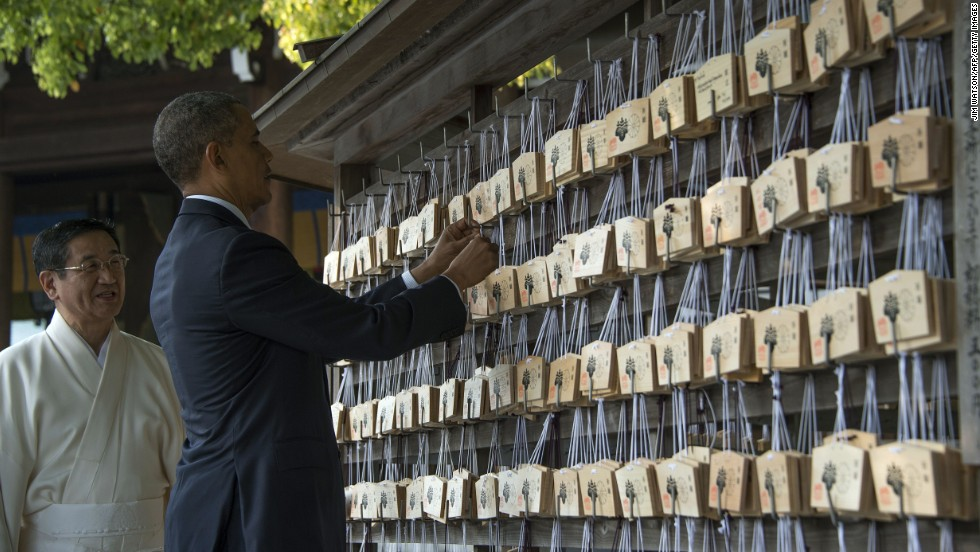 Obama places a prayer tablet on the Votive Tree at the Meiji Shrine.