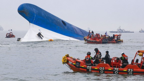 This photo taken at sea some 20 kilometres off the island of Byungpoong in Jindo on April 16, 2014 shows coast guard members searching for passengers near a South Korean ferry (C) that capsized on its way to Jeju island from Incheon.