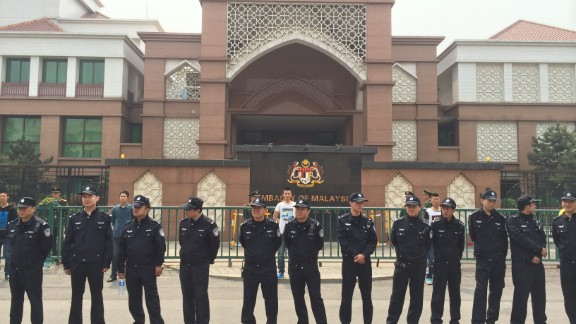 Police surround the building as protesters demand authorities fulfill their promise to answer questions about the missing jet