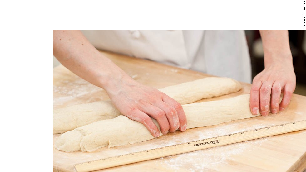 7. Transfer dough to floured work surface, sprinkle top with more flour. Using bench scraper, cut dough in half and gently stretch each half into 16-inch cylinder.