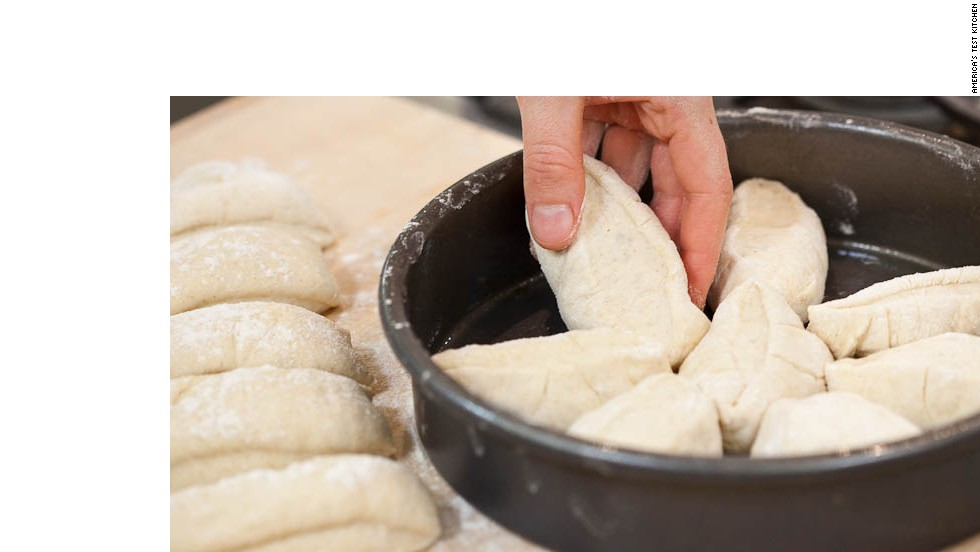 9. With floured hands, gently pick up each piece and roll in palms to coat with flour, shaking off excess, and place in prepared cake pan. Arrange 8 dough pieces, cut-side up, in each cake pan, placing one piece in middle and others around it, with long side of each piece running from center of pan to edge.