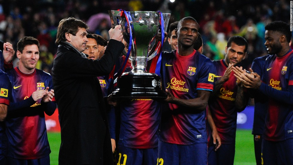 Vilanova and Eric Abidal, who had been diagnosed with a liver tumor, share the honors as they lift the trophy for Barca's 22nd league title.