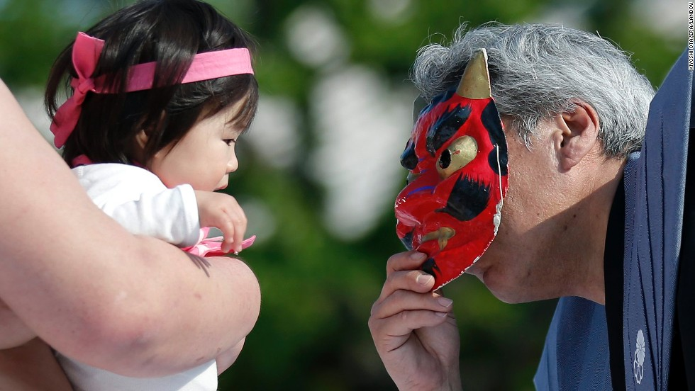 An inspector uses a mask of an <em>oni</em>, or demon, to try to make a baby cry.