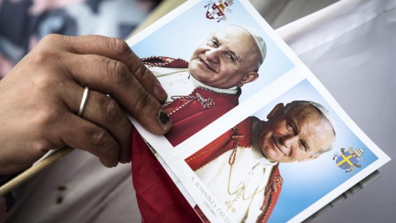 A card shows portraits of John XXIII, left, and John Paul II as pilgrims wait for the canonization ceremony to begin.