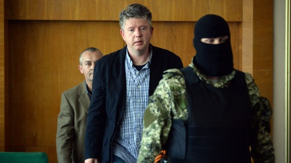 "Detained observers from the Organization for Security and Co-operation in Europe arrive to take part in a news conference Sunday, April 27, in Slovyansk. Vyacheslav Ponomarev, the self-declared mayor of Slovyansk, referred to the observers as ""prisoners of war."""