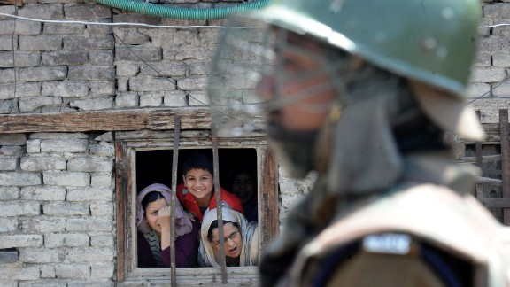 Kashmiri Muslims watch from a window as an Indian paramilitary soldier stands guard near the site of an explosion near the venue where an election campaign rally was to take place in downtown Srinagar on April 27.