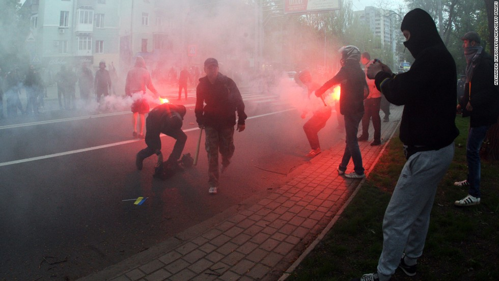 Pro-Russia militants, armed with baseball bats and iron bars, hold flares as they attack people marching for national unity in Donetsk on Monday, April 28.