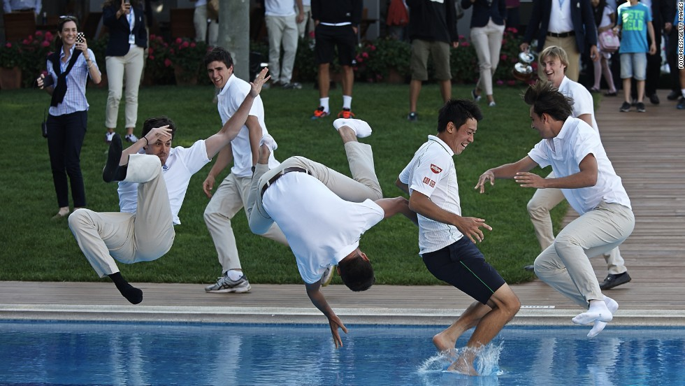 Pro tennis player Kei Nishikori, second from right, is thrown into a pool after winning the final of the Barcelona Open on Sunday, April 27.