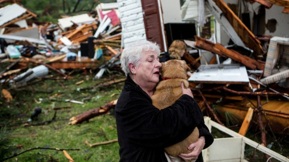 Constance Lambert embraces her dog after finding it when she returned to her destroyed home in Tupelo on Monday, April 28.