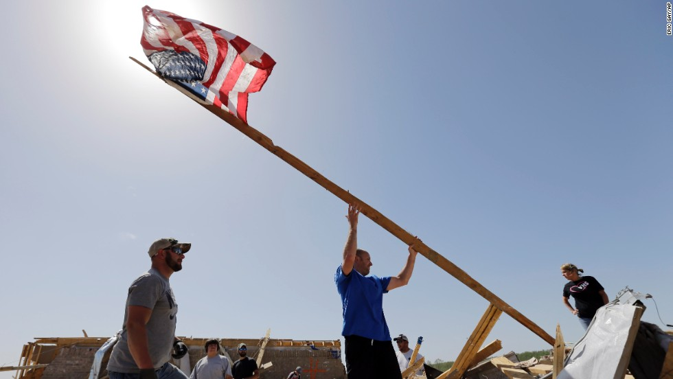 Justin Shaw, left, helps Nick Conway erect a flagpole April 28 at his destroyed home in Vilonia.