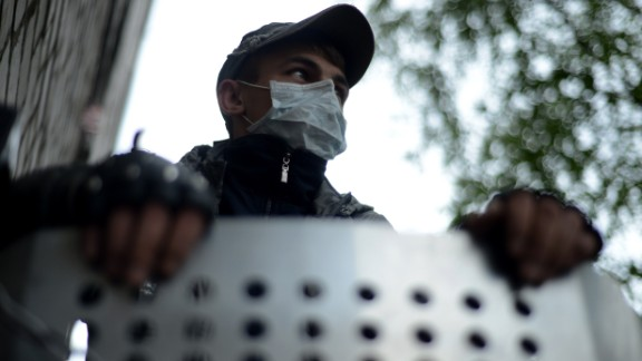 A pro-Russian activist stands at a barricade outside the police regional building seized by the separatists in the eastern Ukrainian city of Slavyansk on April 29, 2014.