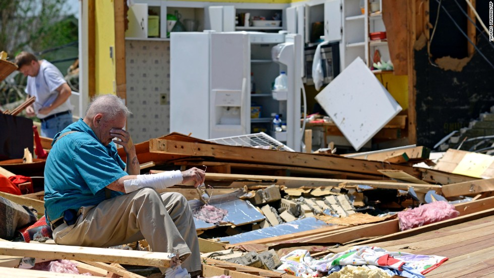 Charles Milam takes a break while searching his destroyed home in Tupelo on April 29.