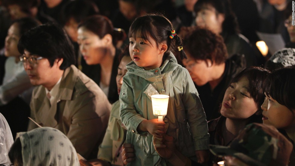 A girl in Seoul holds a candle during a service paying tribute to the victims of the Sewol on Wednesday, April 30.