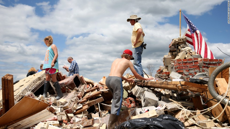 People look for items to salvage from a relative's tornado-ravaged home in Louisville, Mississippi, on Wednesday, April 30.