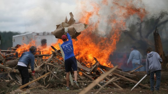 Volunteers throw tornado debris on a burn pile in Vilonia, Arkansas, on April 30.
