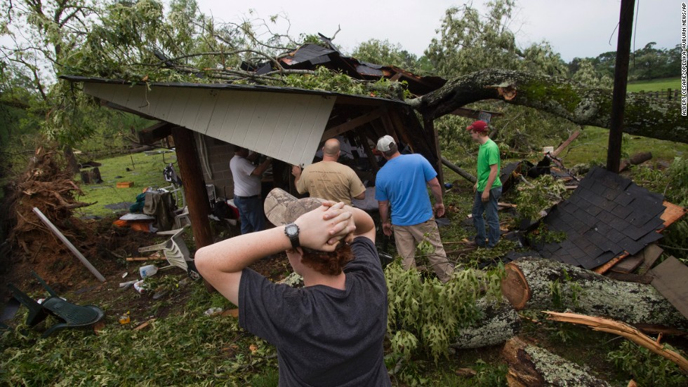People work to clear a tree off a shed after a storm in Smiths Station, Alabama, on April 29.