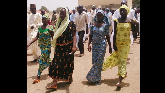 Four female students who were abducted by gunmen and reunited with their families walk in Chibok on Monday, April 21.