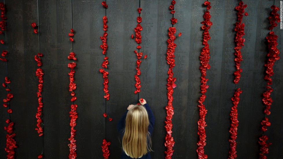 A young girl places a poppy at the Australian War Memorial in Canberra, Australia, on Friday, April 25.
