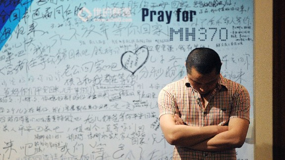 A man stands in front of a  billboard in support of missing Malaysia Airlines flight MH370 as Chinese relatives of passengers on the missing Malaysia Airlines flight MH370 have a meeting at the Metro Park Hotel in Beijing on April 23,