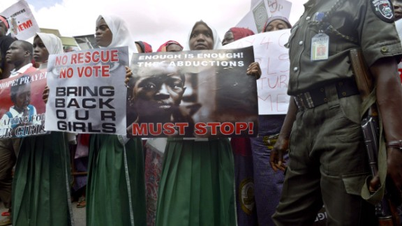 "A policeman stand beside children holding as members of Lagos based civil society groups hold rally calling for the release of missing Chibok school girls at the state government house, in Lagos, Nigeria, on May 5, 2014. Boko Haram on Monday claimed the abduction of hundreds of schoolgirls in northern Nigeria that has triggered international outrage, threatening to sell them as ""slaves"". ""I abducted your girls, "" the Islamist group"