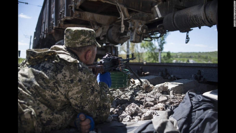 An armed pro-Russian separatist takes a position by the railway lines near Slovyansk on Tuesday, May 6.