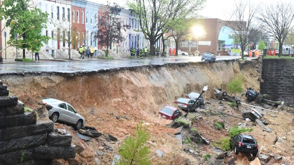 """More than 300 experts helped produce the report over several years, updating a previous assessment published in 2009. A Democratic operative who now counsels the President called the report """"actionable science"""" for policymakers and the public to use in forging a way forward. In this image, cars are seen in the aftermath of an embankment collapse in Baltimore as a massive storm system pounded the mid-Atlantic on April 30."""
