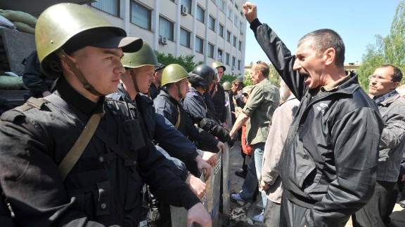 Pro-Russian supporters demonstrate in front of Ukrainian policemen guarding the entrance of a state city building in Mariupol on May 7, 2014.