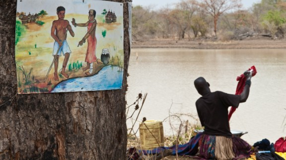 In South Sudan, a woman washes clothes in a roadside dam next to a sign warning of the dangers of spreading Guinea worm disease by entering the water to ease the burning pain caused by an emerging worm.