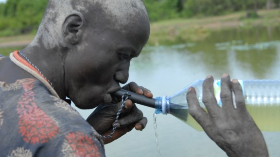 A Southern Sudanese man uses a pipe filter to strain possible water fleas, which could contain Guinea worm larvae, from a potentially contaminated water source.