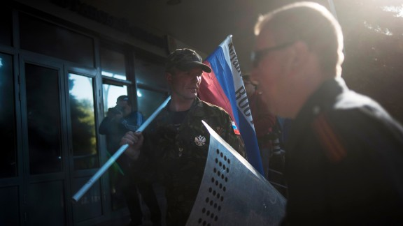 A pro-Russian activist stands with a Russian national flag outside the regional Interior Ministry building in Luhansk on Wednesday, May 7.