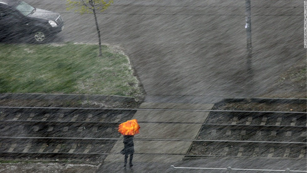 A woman uses an umbrella to shield herself from the snow as she crosses a street in Moscow on Wednesday, May 7.