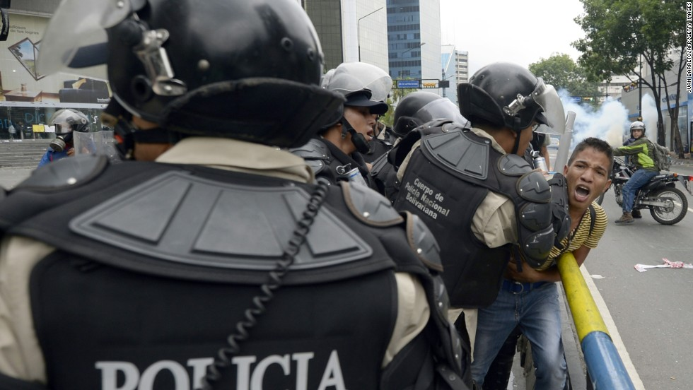 Venezuelan riot police arrest a student taking part in an anti-government protest in Caracas on May 8.