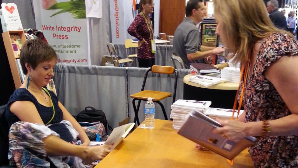 "Kovac has written a book about her journey called ""<a href=""http://www.sarahkovac.com/book"" target=""_blank"">In Capable Arms: Living a Life Embraced by Grace</a>."" She signs it with her feet."