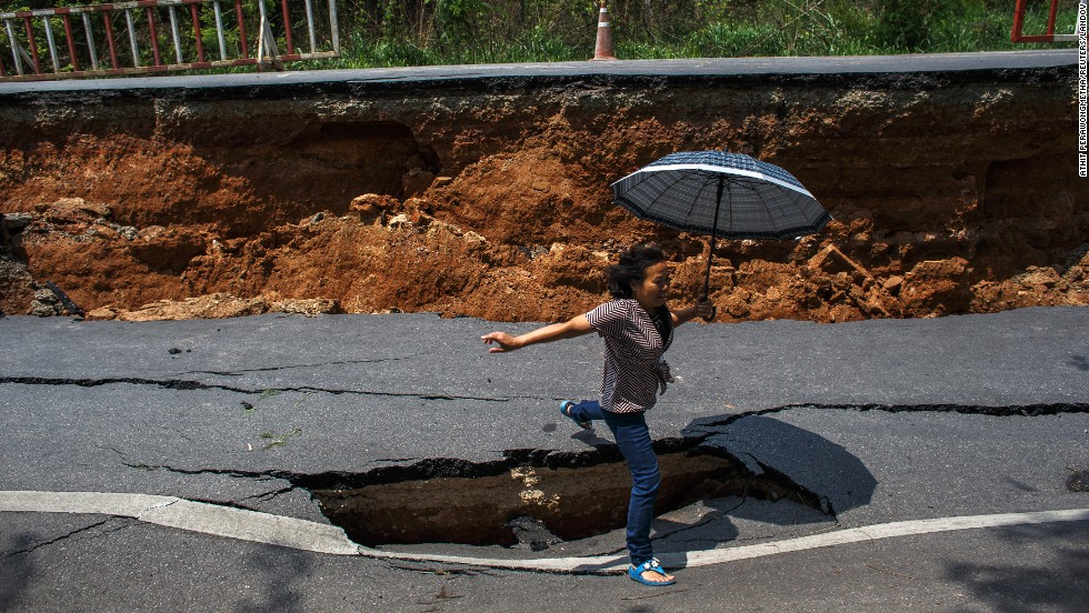 A woman jumps over a hole Tuesday, May 6, on a highway road that was damaged by an earthquake in Chiang Rai, Thailand. The 6.0 magnitude earthquake shook northern Thailand the day before, causing some damage to roads and buildings.