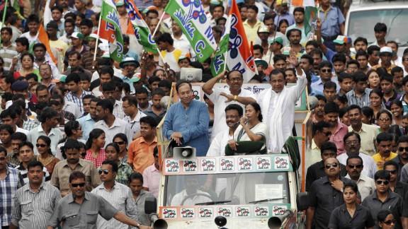 Trinamool Congress Chairwoman Mamata Banerjee, with microphone, campaigns for Jadavpur TMC candidate Sugata Bose, left, and South Kolkata candidate Subrata Bakshi, center, with Mithun Chakraborty on May 10 in Kolkata.