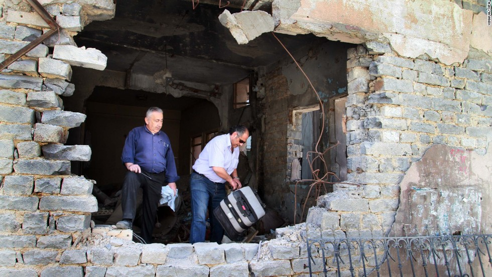 Residents return to damaged dwellings in Homs on May 10.