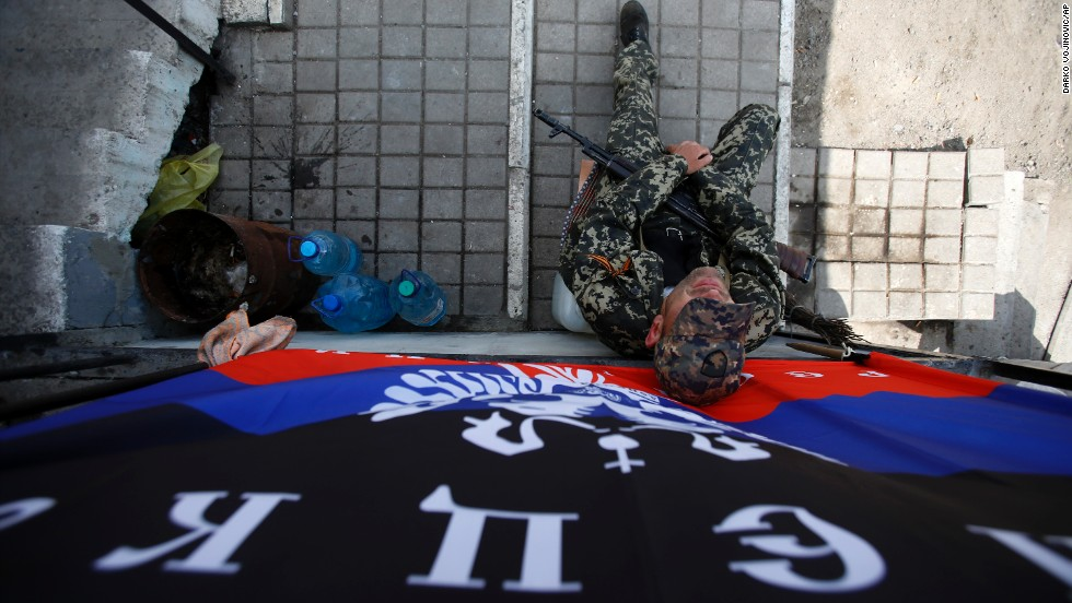 An armed pro-Russian man sits below a flag of the self-proclaimed Donetsk People's Republic at the barricades on a road leading into Slovyansk on May 11.