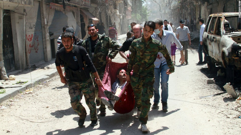 Rescuers carry a man wounded by a mine in the Bustan al-Diwan neighborhood of Homs on Saturday, May 10, as thousands of Syrians returned to the city.