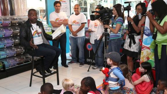 "Burton reads to children during the ""Reading Rainbow"