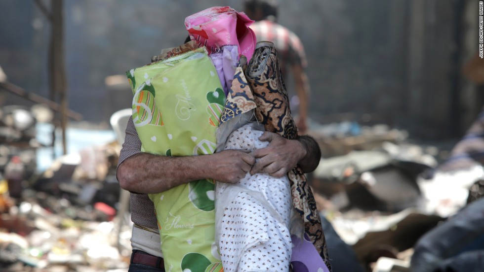 A man carries rolls of cloth out from a destroyed building in Homs on May 12.
