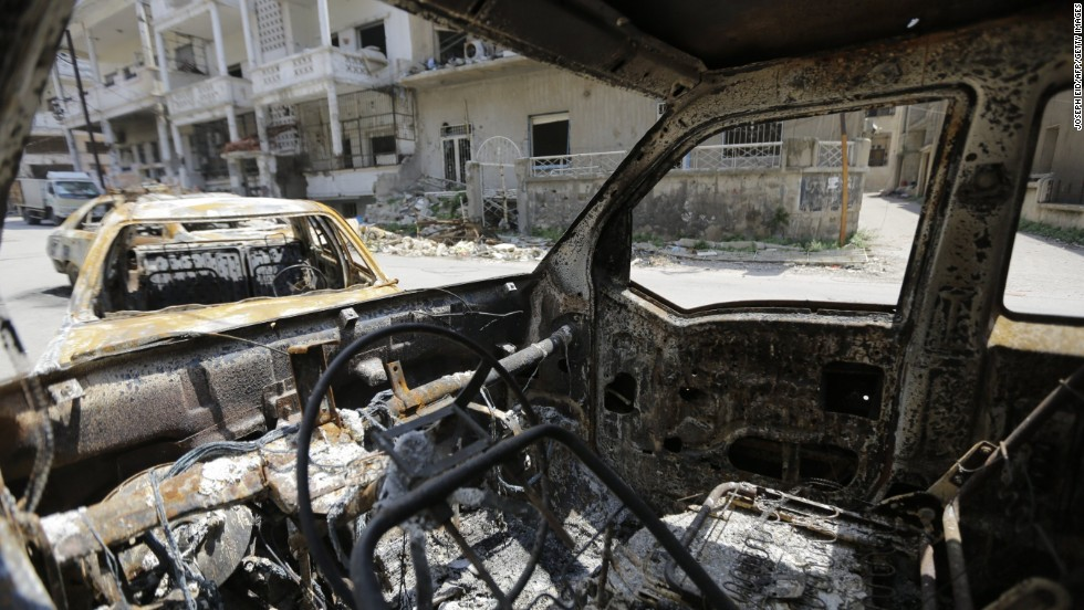 Destroyed vehicles line the streets of Homs on May 12.