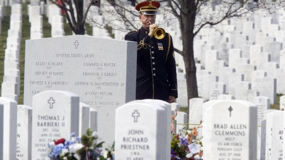 An Arlington National Cemetery Honor Guard bugler plays taps during funeral services for Army Spc. Ross Andrew McGinnis, who was killed in Iraq in December 2006.