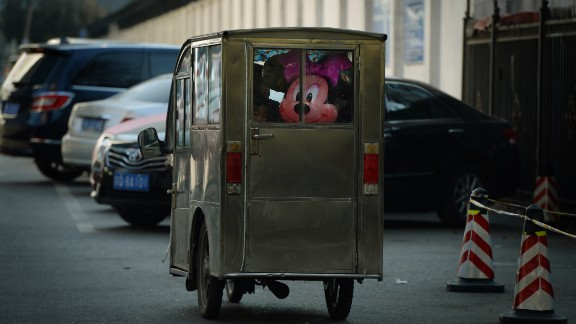 But not everyone is enchanted by the motorized rickshaws, as many see them as a relic of the past and as a traffic-congesting and pollution-emitting nuisance. This shows a Minnie Mouse in the back of a Chinese motorcycle taxi.
