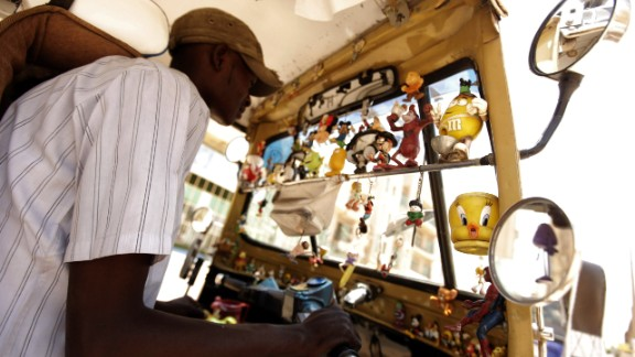 The motorized taxis also carry distinctive flavor like this Sudanese driver who steers an India-made vehicle, full of toys and knick knacks.