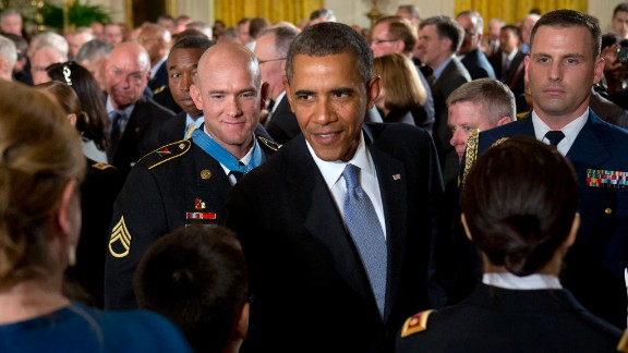 """Army Staff Sgt. Ty M. Carter, left, watches as Obama greets family members of fallen service members after Carter was awarded the Medal of Honor in August 2013. Carter was cited for his actions during the October 3, 2009, defense of Command Outpost Keating in Afghanistan, including """"running through a hail of enemy rocket propelled grenade and machine gun fire to rescue a critically wounded comrade."""""""