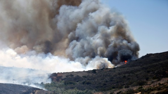 Billowing smoke rises as firefighters trek up the hills to battle a San Diego fire on May 13.