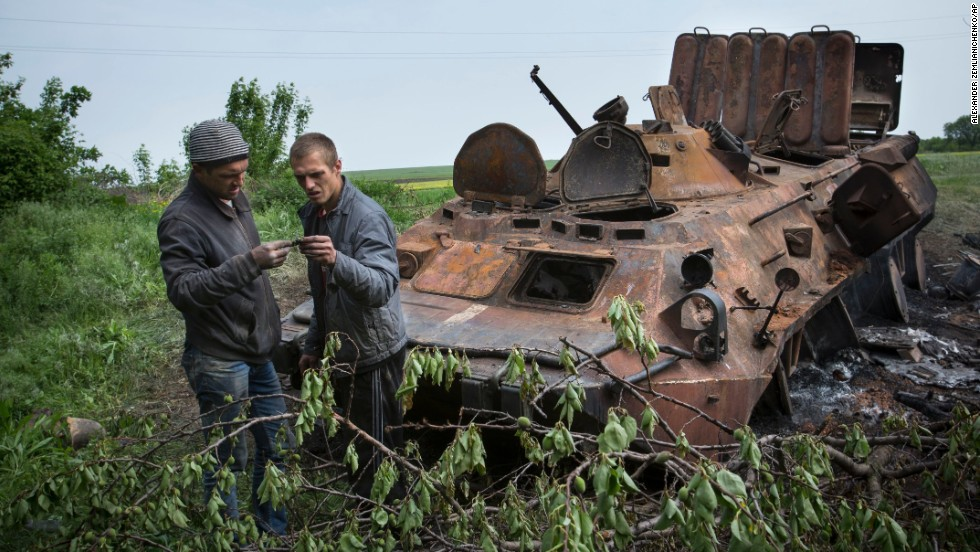Two men collect parts of a Ukrainian armored personnel carrier, destroyed May 14 in what the Ukrainian Defense Ministry called a terrorist attack near Kramatorsk.