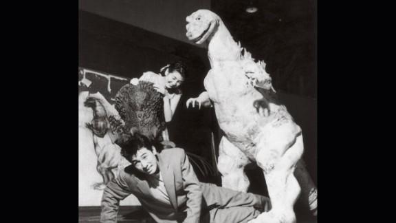 """Godzilla"" stars Akira Takarada, bottom, and Momoko Kochi clown around at Toshimitsu's fabrication studio with the unfinished monster costume in 1954."